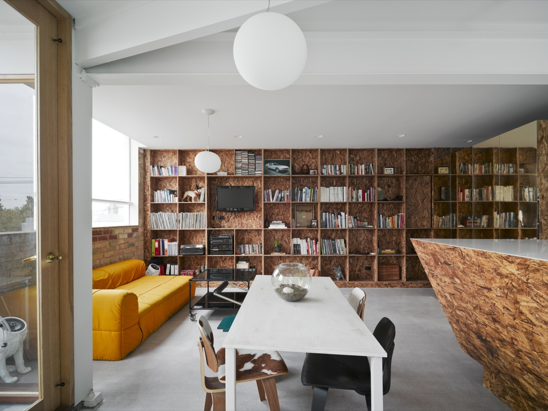 Oriented strand board bookshelves take up the entire wall of the small but not cramped living area in the project Cubby House