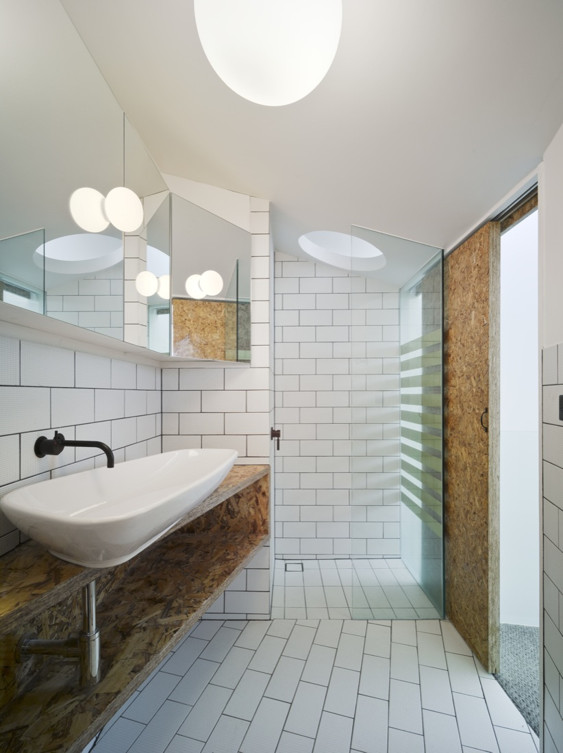 Bathroom in white and oriented strand board feels light and airy at the Cubby House project