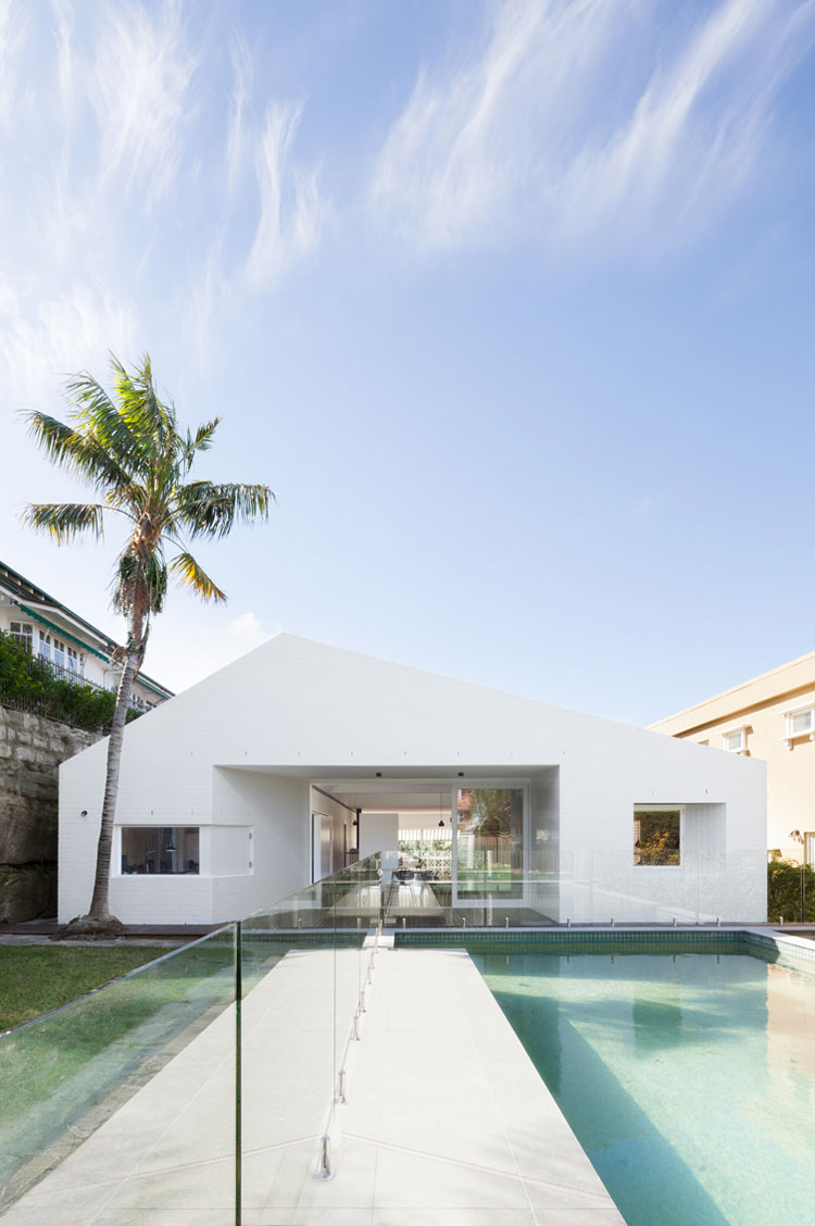 A minimalist white facade compliments a pool in the backyard of House Capple