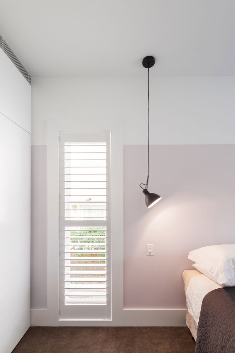 A simple reading lamp hangs from the ceiling in the bedroom -- a fun choice of lighting